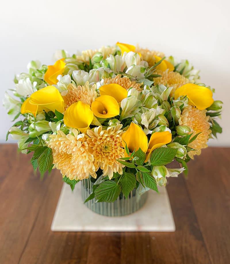composition florale composé de bonnys jaunes, callas et alstroemerias blancs